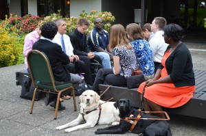 Participants of the Empowering Blind Students in Science and Engineering workshop and a couple of guide dogs mingling outside.